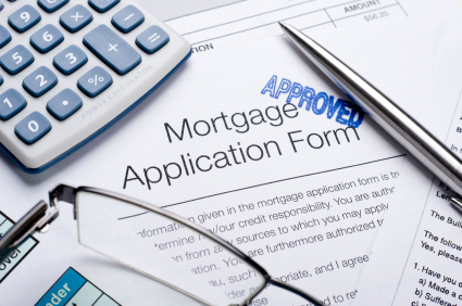 Approved Mortgage application form with a calculator and pen