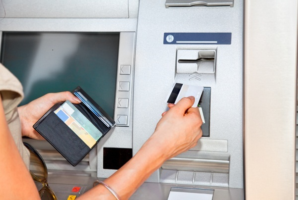 Woman's hand inserting plastic card Visa into the ATM
