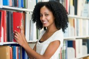 University student selecting book in library