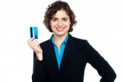 Smiling businesswoman holding a credit card