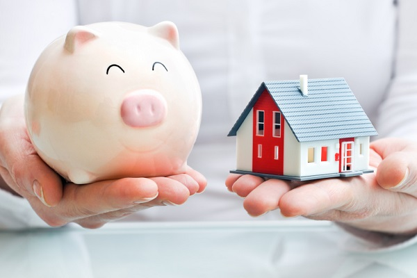 holding piggy bank and model house in hands