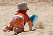 toddler chasing ball on the beach