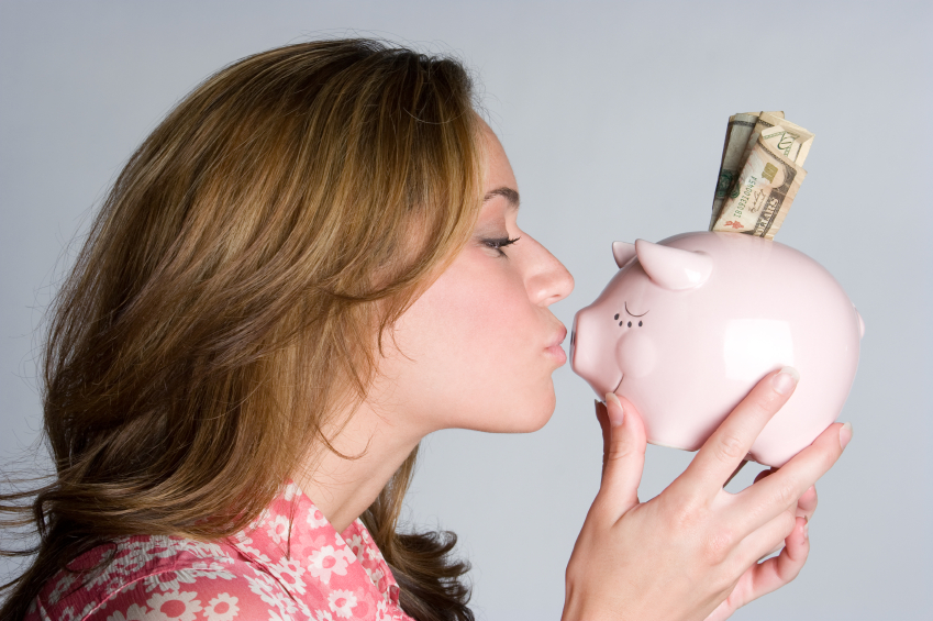 woman saving money and kissing piggybank