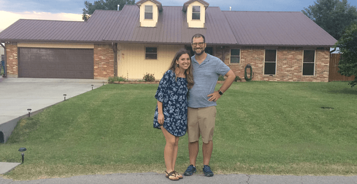 Kara and husband in front of home